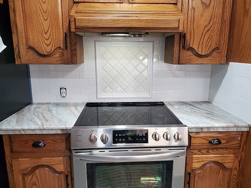 Countertop: 2CM Fantasy Brown Polished Exotic Marble, Backsplash: 3x6 Bright White Ice Subway Tile, Stove Splash: White Arabesque Tile Outlined with Bright White Ice Chairrail