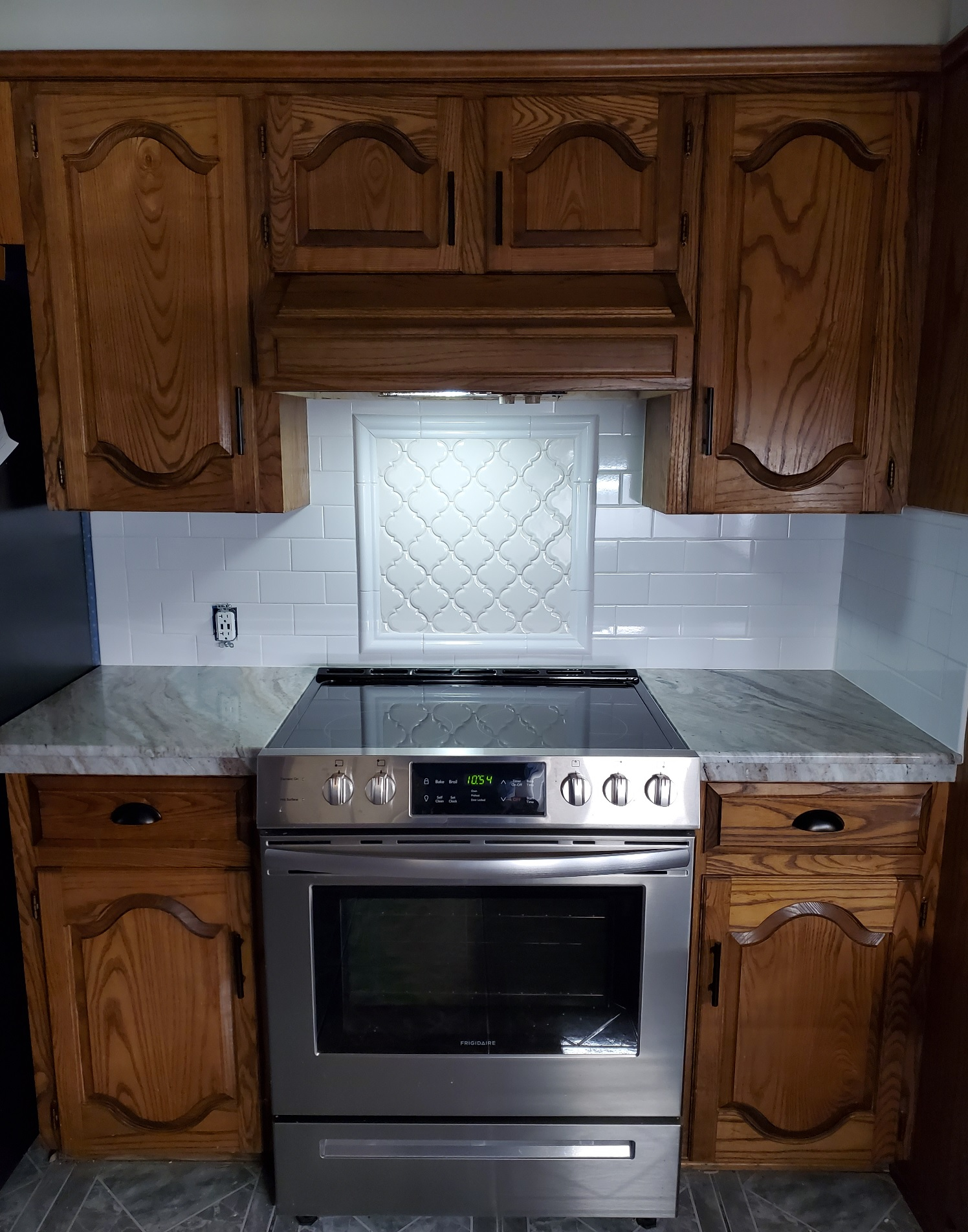 Countertops: 2CM Fantasy Brown Polished Exotic Marble, Backsplash: 3x6 Bright White Ice Subway Tile, Stove Splash: White Arabesque Tile Outlined with Bright White Chairrail